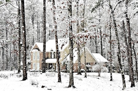 An executive home graced with falling snow on a cold winters day Stock Photo