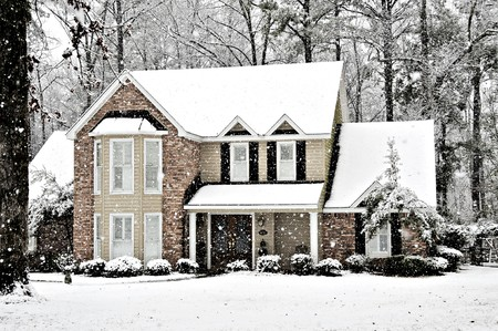 Winter snow falling on an executive home
