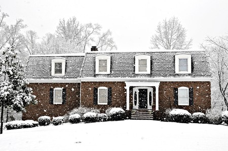 Snow falling on an executive home on a cold winter day