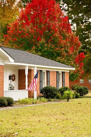 Ranch introductie omgeven met val bomen en een Amerikaanse vlag Stockfoto