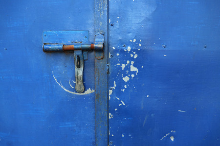 Blue padlock old door with rust from being born to rain frequently. Banco de Imagens