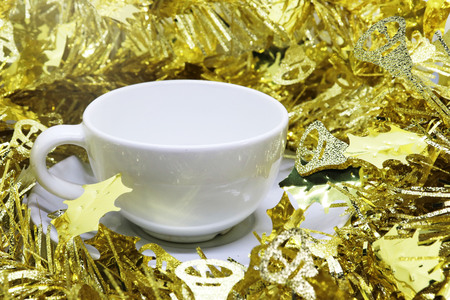 Gold ribbon surrounded ceramic coffee cups, empty.