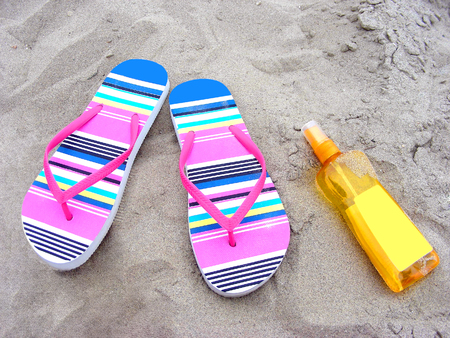 Summer time with flip-flops and suncare milk on a sandy beach