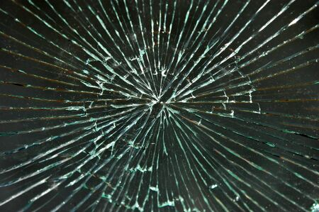 Shattered dirty windshield glass on a black background
