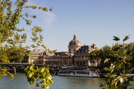academie: The Dome of the Academie Francaise viewed across the river Seine from the Right Bank. Crowds line the Pont des Arts and a tourist boat is moored on the Left Bank.