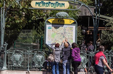cite: Three tourists point to metro map at Cite stop on Ile de la Cite, Paris. Editorial