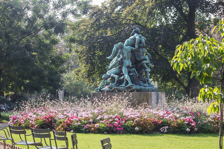 bacchus: Statue of Bacchus seen from the side, with base surrounded by flower beds.Summer foliage.