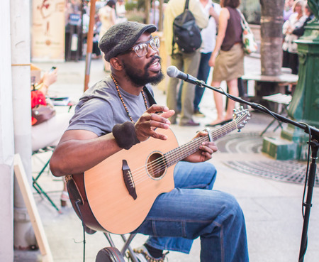 itinerant: Kuku, itinerant folk musician, playing guitar and singing outside Shakespeare and Company in Paris, France Editorial