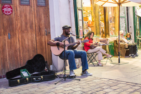 itinerant: Kuku, itinerant folk musician, playing guitar and singing outside Shakespeare and Company in Paris, France. Customers sit and read at adjacent cafe tables
