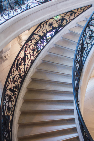 ironwork: Portion of the curving circular staircase with delicate ironwork railings, marble stairs, in the Petit Palais, Paris, France