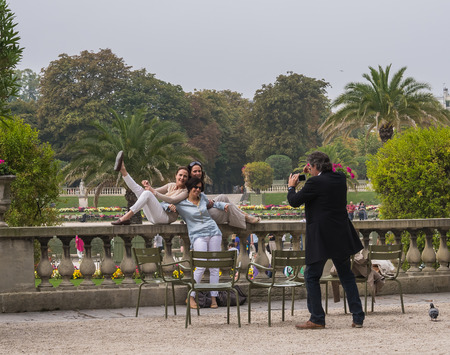 clowning: Man in blazer and jeans photographs women striking funny group pose on stone wall in Jardin du Luxembourg, Paris, France