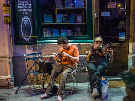 hemingway: Two men sit in cafe chairs outside Shakespeare and Company, famous bookstore in Paris, and concentrate on their reading. Barefoot man reads Hemingway; older gentleman reads magazine.