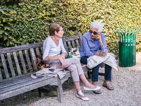 older women: Older women friends talk on a bench in a Paris park, France.