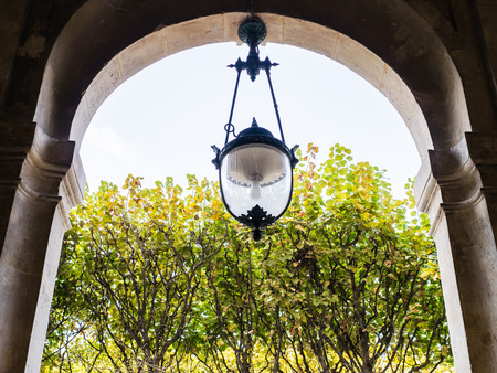 ironwork: Ironwork lamp hangs in archway in Palais Royal, Paris, France, with foliage in background Editorial
