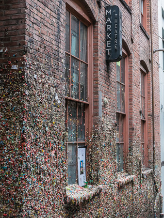public market sign: Market Theatre sign above brick wall covered in chewed gum wads, Seattle Editorial