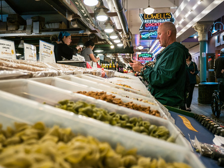 pike place: Male customer in windbreaker pulls credit card from wallet in front of pasta display in Pike Place Public Market Seattle