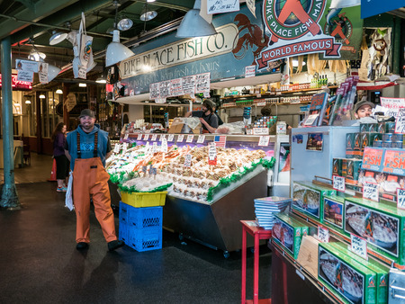 pike place: Worker smiles for camera in front of busy displays of iced and dried fish at Pike Place Fish Company Public Market Seattle.