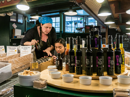 pike place: two women workers arrange vinegars at pasta counter Pike Place Public Market Seattle Editorial