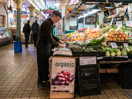 pike place: Aproned male worker arranges merchandise at organic produce stall at Pike Place Public Market Seattle