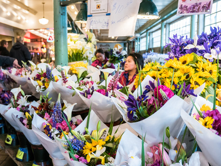 pike place: Bouquets of colorful flowers for sale at Pike Place Public Market in Seattle workers in background