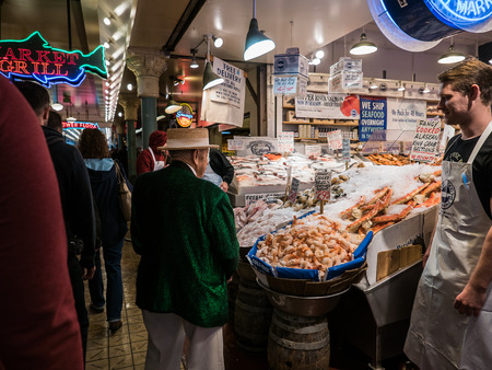 pike place: Senior man in boater and green jacket looks at seafood counter at Pike Place Public Market Seattle