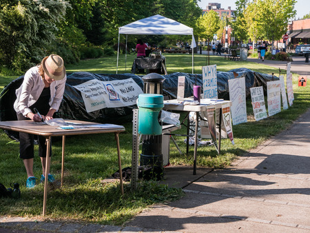lng: Anti-pipeline demonstration at Corvallis Oregon Farmers Market, Spring 2015. Protest signs and black plastic pipeline displayed.