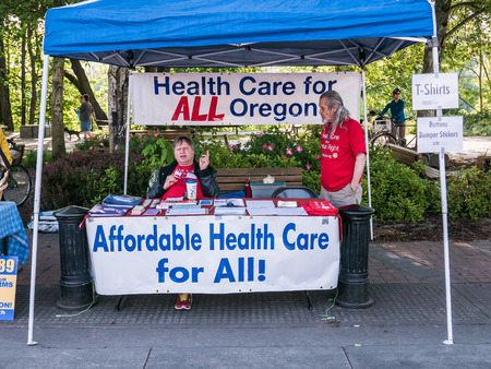 funded: Volunteers working for publicly funded health care staff booth at Corvallis Farmers Market in Oregon, Spring 2015