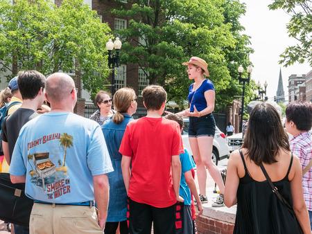 tour guide: Cambridge, MA, 12 de Junio, 2015: Mujer gu�a presenta informaci�n al grupo en Harvard Square fuera de Harvard Yard, Cambridge, Massachusetts. Editorial