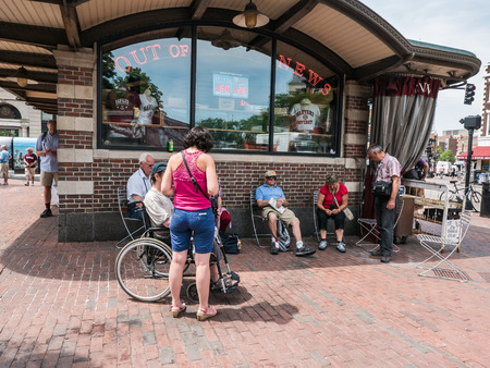 patio chairs: Cambridge, MA, June 12, 2015: Tourists rest in patio chairs outside Out of Town News stand in Harvard Square