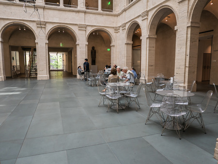 art museum: Cambridge, MA, June 12, 2015: Patrons relax at steel cafe tables in the Fogg Art Museum courtyard at Harvard University