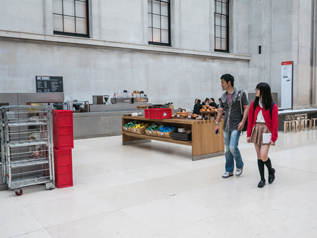 british museum: London, England, August 20, 2015: Visiting couple stroll past courtyard cafe in the Great Court of the British Museum.