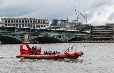 blackfriars bridge: London, England, August 20, 2015: red-jacketed pilots wave from Thames Rockets tourist boat near Blackfriars Bridge, Thames River