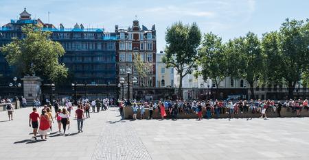 puertas de hierro: Londres, Inglaterra, el 22 de agosto, 2015: Los peque�os visitantes se sientan en una pared de piedra fuera del Museo Brit�nico en una tarde de agosto; multitudes vierten dentro y fuera de las puertas de hierro Editorial