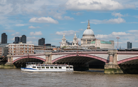 blackfriars bridge: London, England, August 21, 2015: Ferry passes under Blackfriars Bridge; St. Pauls Cathedral in background