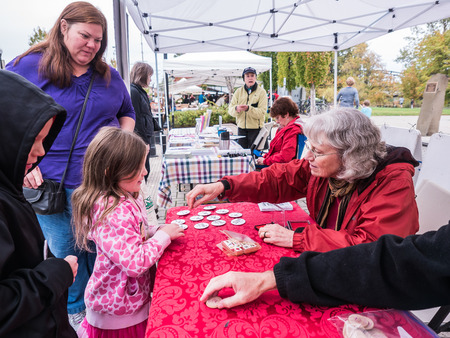 tokens: Corvallis, Oregon, October 24, 2015: Children receive Food Day hand stamps and tokens from volunteers at Corvallis Farmers Market