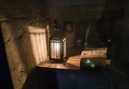 political prisoner: Paris, France, August 29, 2015: Lamp and book scene is recreated in a prisoners cell in 18th-century Conciergerie