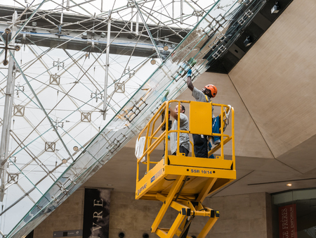carrousel: Paris, France, Sept 1, 2015: Window washers clean inverted pyramid in the Carrousel du Louvre