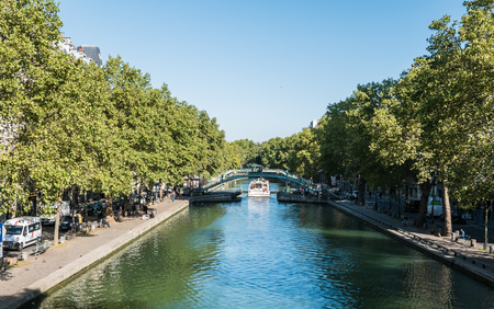 pedestrian bridge: Paris, France, Sept 3, 2015: Canauxrama canal boat passes under a pedestrian bridge on Canal Saint Martin