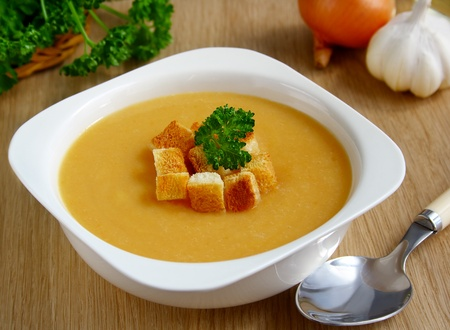 croutons: A bowl of pea cream soup with croutons on the dining table.