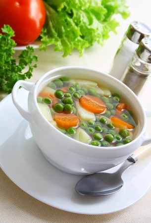 vegetarian soup with green peas. carrot, and potatoes on a table.