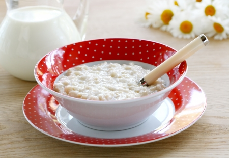 Useful milk porridge for breakfast in a red bowl on wooden table  photo