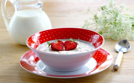 Milk porridge with strawberries in a red bowl on wooden table    photo