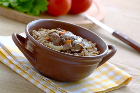 second meal:  Buckwheat porridge with stewed liver in a brown bowl on a wooden table.