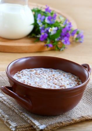 Buckwheat porridge with milk in a brown bowl on wooden table photo