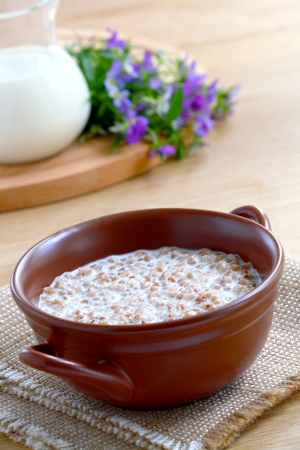 Buckwheat porridge with milk in a brown bowl on wooden table Stock Photo - 14494307
