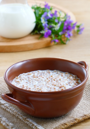 Buckwheat porridge with milk in a brown bowl on wooden table Stock Photo - 14494300