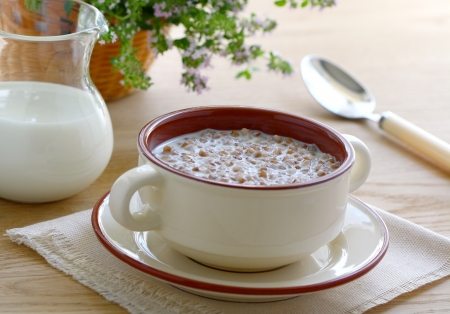 Buckwheat porridge with milk in a bowl on wooden table photo