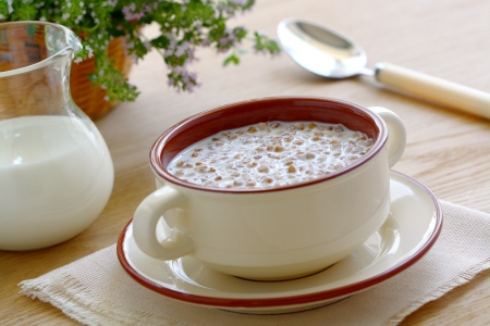 Buckwheat porridge with milk in a bowl on wooden table