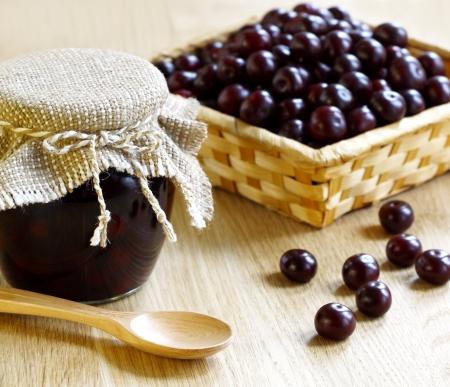 mermelada: Mermelada de cerezas en frascos de vidrio sobre una mesa de madera