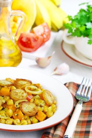 platanos fritos: Calabaza con garbanzos y pl�tanos fritos en un plato sobre la mesa